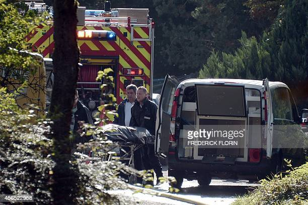 Medics load a victim's body into an ambulance on October 2 2014 at the site where a helicopter from Switzerland crashed in the eastern French village...