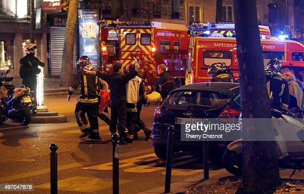 Medics move a wounded man near the Boulevard des FillesduCalvaire after an attack November 13 2013 in Paris France Gunfire and explosions in multiple...