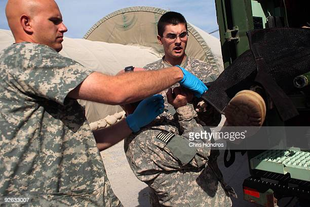Medics pull out the guerney carrying a grievously wounded unidentified Afghan National Army soldier at Kandahar Air Field's trauma center November 1...