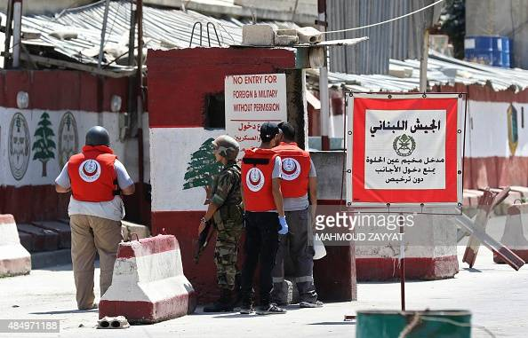 Medics wearing flak jackets wait at the entrance of the Ain ElHelweh Palestinian refugee camp near Lebanon's southern port city of Sidon during...