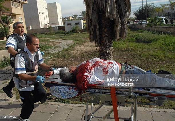 OUT Medics wheel an Israeli wounded man after a rocket launched from the Gaza Strip hit the southern Israeli town of Netivot on December 27 2008...