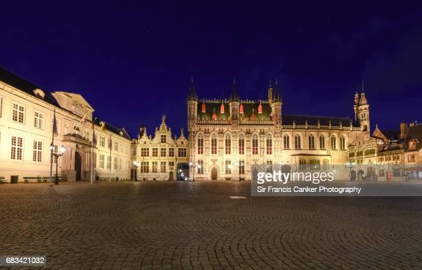 Medieval Burg square in Bruges, Flanders with town hall and Basilica of the Holy Blood illuminated at late dusk in Flanders, Belgium