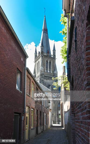 Medieval church spire seen from narrow old town street in Bruges, Belgium