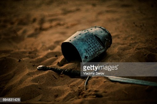 Medieval helmet and sword in sand