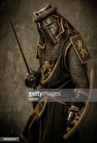 Medieval knight metal mesh armor sword shield posing scary : Stock Photo