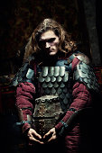 Medieval knight in the armor with the helmet. Portrait in the shadows.