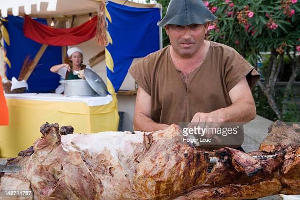 Medieval man carving roast pig at Columbus Festival Celebration.
