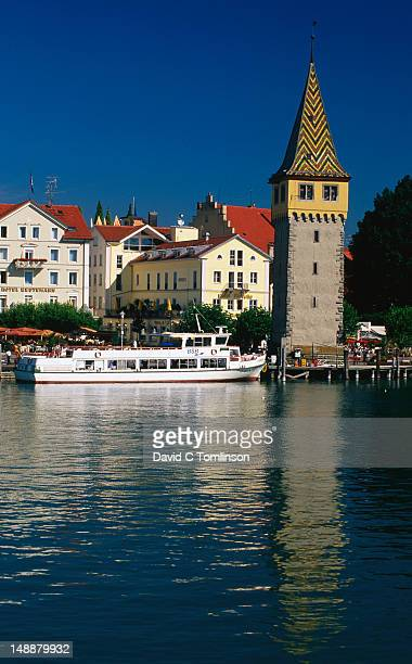 Medieval Mangturm (lighthouse) and harbour ferry on Lake Constance.