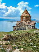 View of Sevanavank monastery and Sevan lake surrounded by snowy mountains in Armenia
