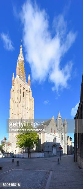 Medieval street in Bruges with majestic 'Church of our Lady' brick-built bell tower and gothic facade in Flanders, Belgium