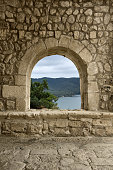 A window/arch at the entrance of a romanesque church in a spanish village (Castellet, Barcelona). A beautiful landscape may be seen through it.