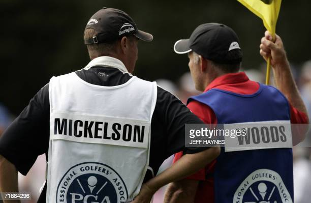 The caddies for golfers Phil Mickelson and Tiger Woods Jim MacKay and Steve Williams talk on the 16th green 17 August 2006 during the first round of...
