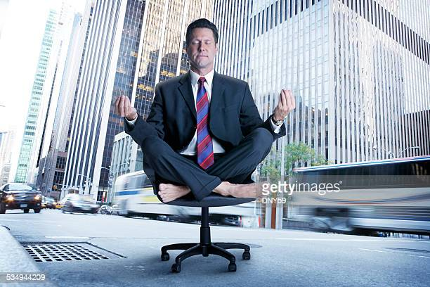 Meditating Businessman In The Middle Of A Busy  City Street