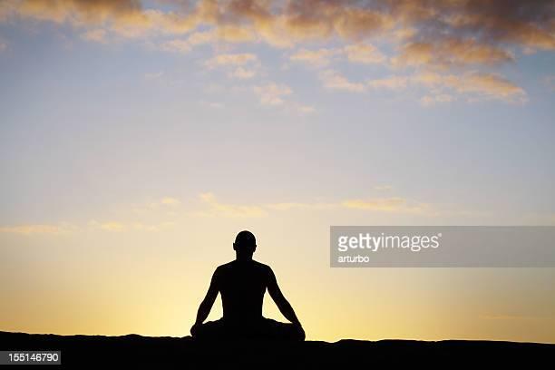 meditating man against sky