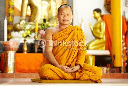 Meditating monk in a sacred shrine : Stock Photo