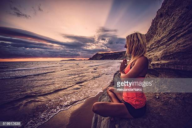 Meditating on the beach rock in a fire log pose
