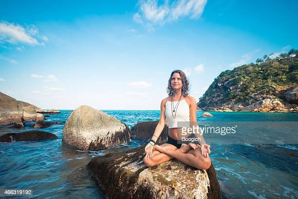 Meditating Woman Sits in Yoga Lotus Pose on Ocean Rock