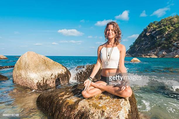 Meditieren Frau sitzt in Yoga Lotus-Pose am Meer Rock