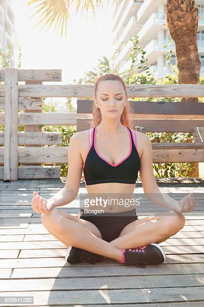 Meditating Woman Sits Outdoors in Fitness Clothes with Eyes Closed