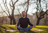 Mature man sitting on yoga mat in comfortable asana smiling and relaxing in park.