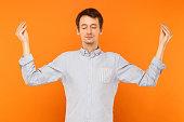Meditation, mental practice. Young adult man closed eyes and doing yoga. Studio shot, orange background