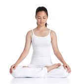 female asian teenager doing meditation against white background