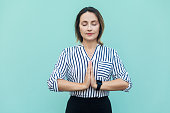 Meditation, religion and spiritual practises. Beautiful business woman doing yoga indoors at light blue wall, keeping eyes closed, holding fingers in mudra gesture. Isolated studio shot.