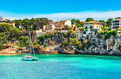 Beautiful view of bay with sailing boat at the seaside of Porto Cristo on Mallorca, Spain Mediterranean Sea
