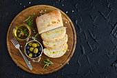 Mediterranean snacks set. Green and black olives, olive oil, herbs and sliced ciabatta bread on wooden board over dark stone background. Italian food concept. Top view. Copy space.