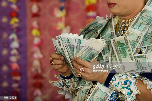 A medium counts money offered by revellers during a dance at the Taungbyon nat festival Every year in August hundreds of thousands of people from all...