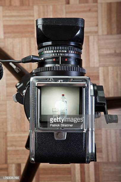 A medium format camera photographing a glass next to bottled water