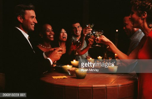 Medium group of people dining and toasting at restaurant