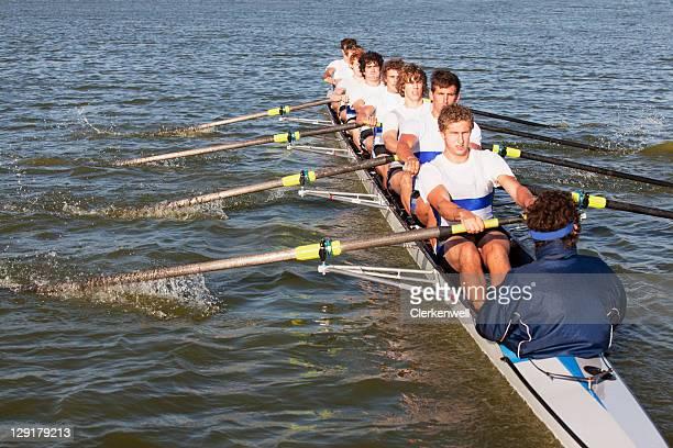Medium group of people oaring canoe