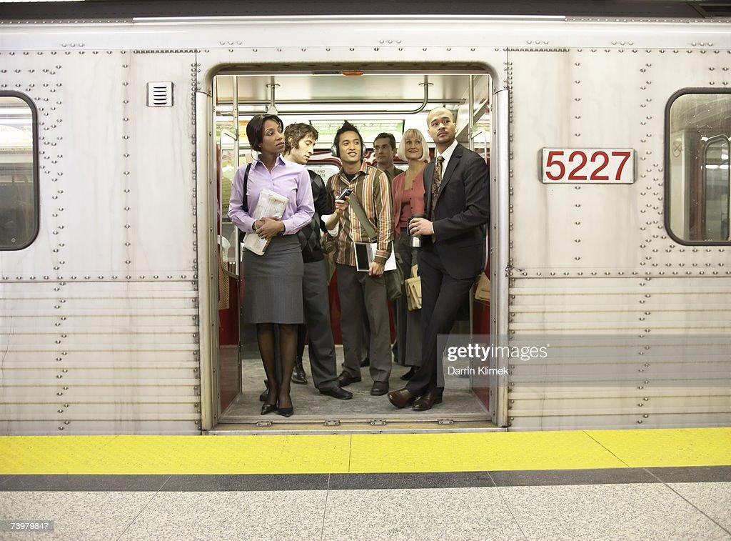 Medium group of people standing in subway train doorway