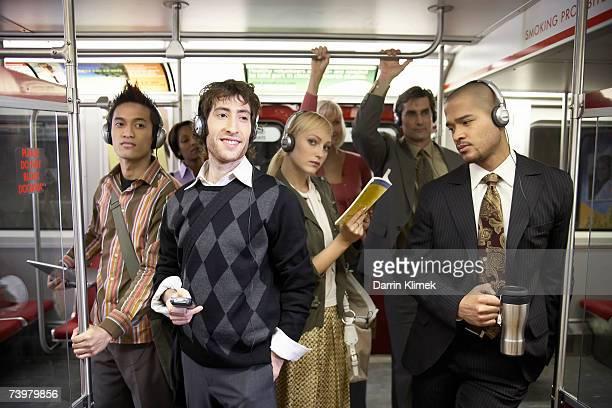 Medium group of people standing in subway train, wearing headphones