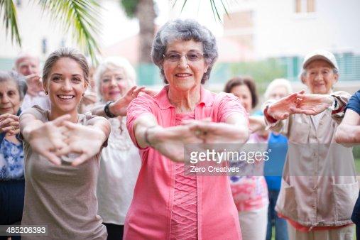 Medium group of seniors exercising in retirement villa garden