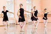 Medium group of teenage girls in black dresses practicing ballet moves in large dancing studio.