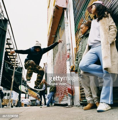 Medium Group of Teenagers in a Back Alley Watching Stunts on a Skateboard