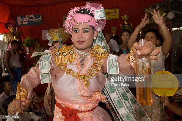 A medium holding a bottle of whisky and a cigarette dances in one of the numerous shrines dedicated to the nats during the Taungbyon nat festival...
