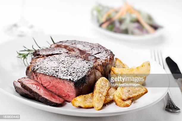 Medium rare ribeye steak with side of seasoned potato fries