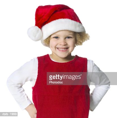 medium shot of a cute female child in a santa hat as she puts her hands on her hips and smiles : Foto de stock