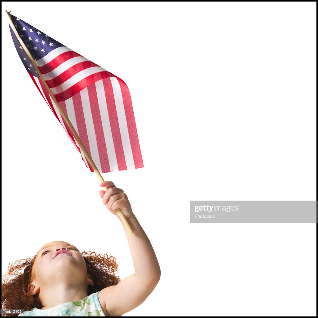 medium shot of a female child as she looks up and waves an american flag