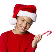 medium shot of a female child in a santa hat as she holds out a candy cane