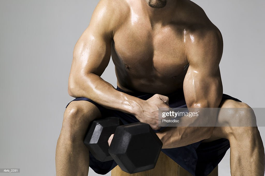 medium shot of a male bodybuilder as he lifts a weight : Stock Photo