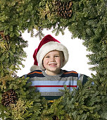 medium shot of a male child in a santa hat as he sits in the middle of a christmas wreath