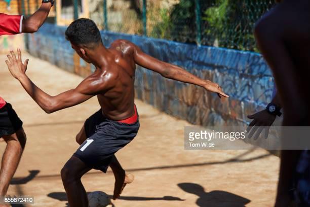 Medium shot of a strong, young, dark skinned man playing football