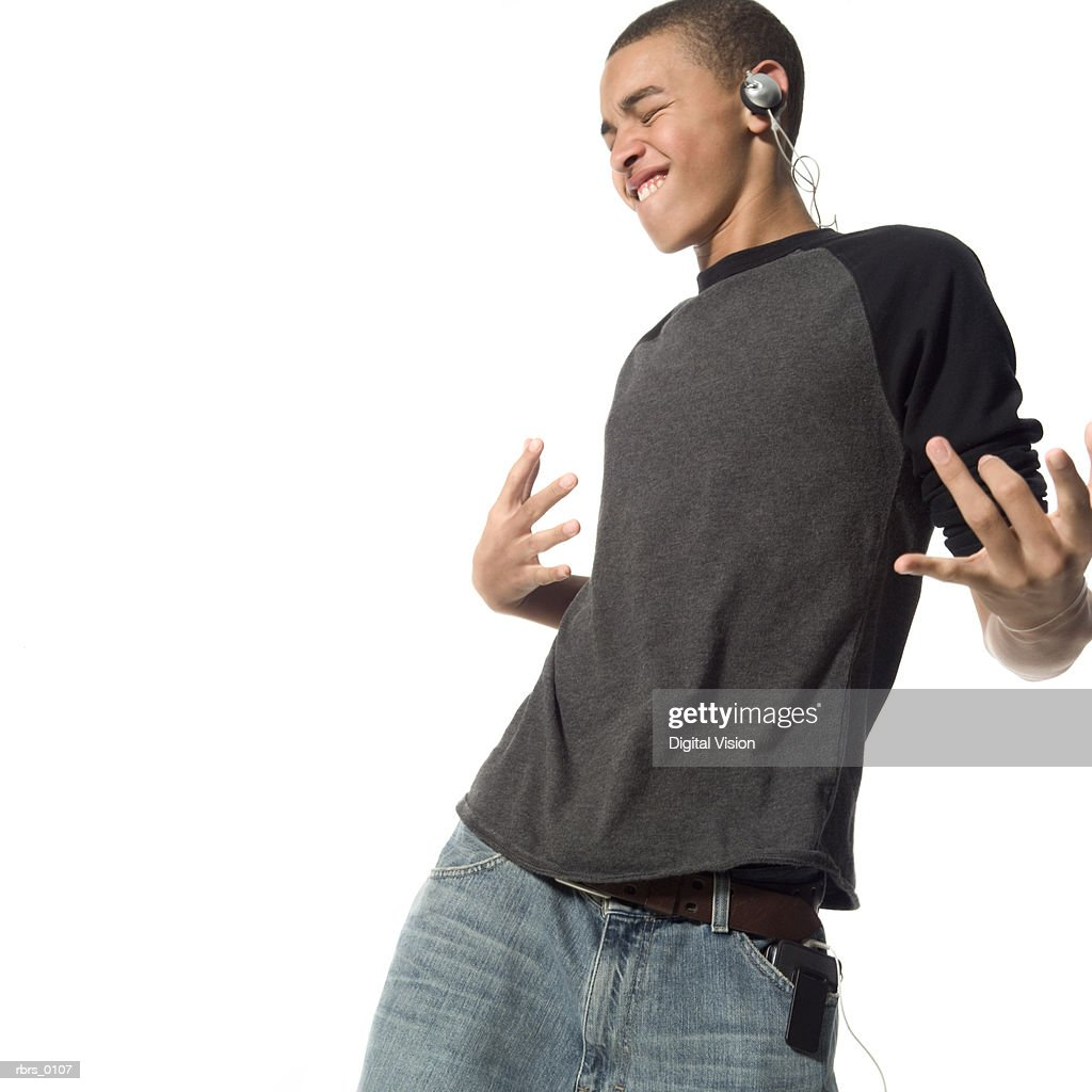 medium shot of a teenage male as he dances wildly while listening to headphones : Stock Photo