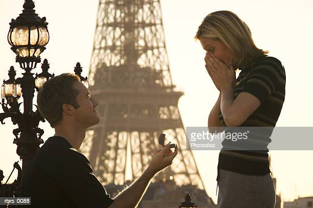 medium shot of a young adult couple as the man proposes in front of the eiffel tower in paris