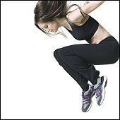 medium shot of a young adult woman in a black exercise outfit as she jumps up