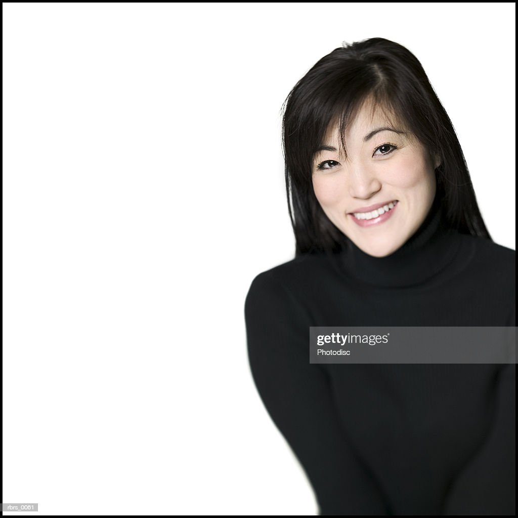 medium shot of a young adult woman in a black sweater as she smiles : Stock Photo